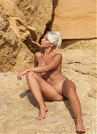 young blonde girl shows off on the sedimentary rocks