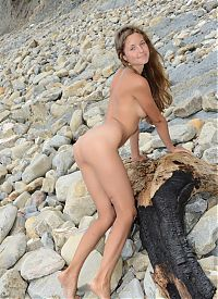 Babes: cute young dark blonde girl with blue eyes and natural untrimmed pubic hair reveals her dress on the driftwood washed up on the rocky beach