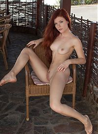 Babes: young red haired girl with facial freckles reveals her top and panties at the table with the rattan chair