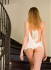Babes: young blonde girl reveals her white chemise and gee string panties on stairs at home