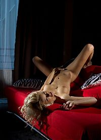 Babes: young curly blonde girl with feathered hairstyle reveals her undergarments on the red couch at home