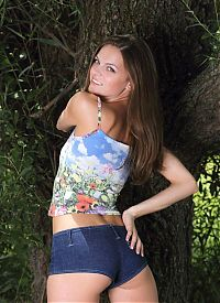 Nake.Me search results: young brunette girl with blue eyes reveals her short jeans and top in the nature under the tree