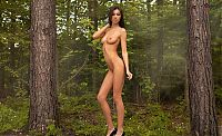 young brunette girl reveals her black bikini on the forest nature trail