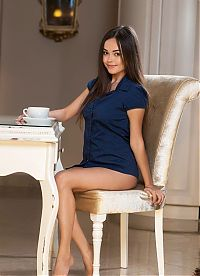 young brunette girl with a coffee reveals her blue shirt on the chair