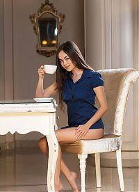 Nake.Me search results: young brunette girl with a coffee reveals her blue shirt on the chair