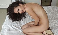 curly brunette girl shows off on the bed at home