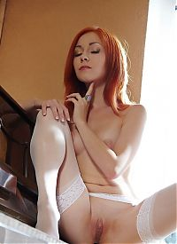 Nake.Me search results: red haired girl reveals her hold-ups with garter belts suspenders on the couch at home