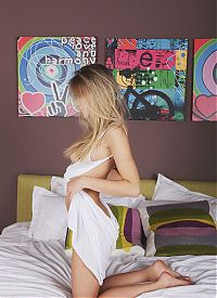 Babes: young blonde girl reveals her white nightgown and pubic hair landing strip on the bed