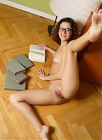 Nake.Me search results: curly brunette girl with glasses reveals her shirt at the chest of drawers with books