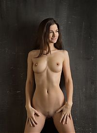 young brunette girl reveals her pubic hair landing strip on the taboret in the studio