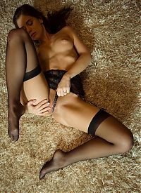 Nake.Me search results: young brunette girl reveals her black stockings with garter belts suspenders on the fur carpet