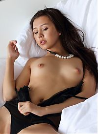 Nake.Me search results: young asian girl with a pearl necklace reveals her black transparent chemise and panties on the bed