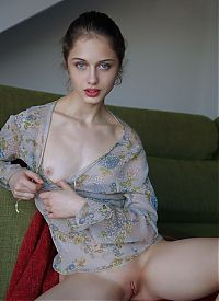 cute young dark blonde girl with blue eyes reveals her negligee on the green couch at home